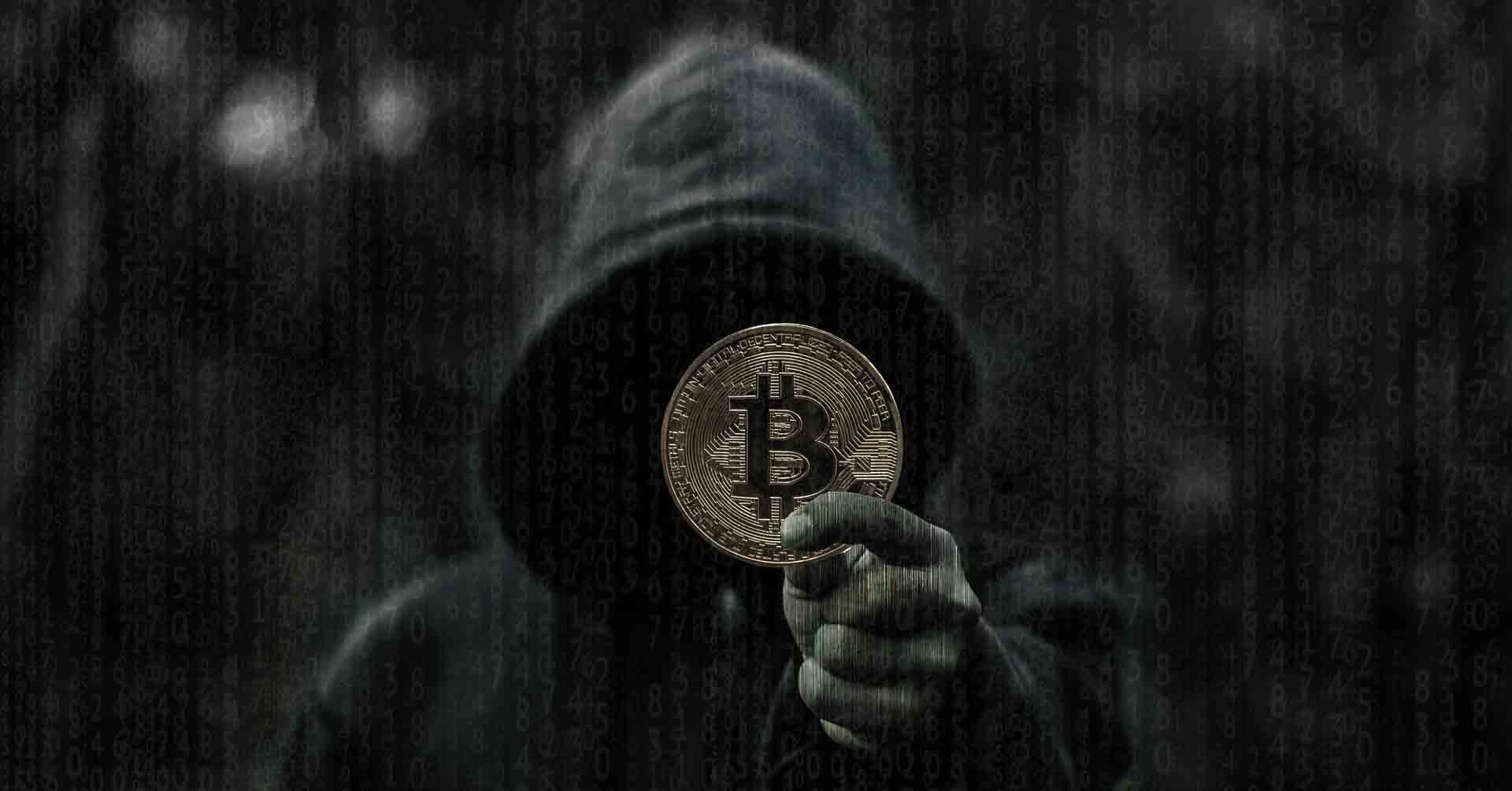 Anonymous man holding a bitcoin